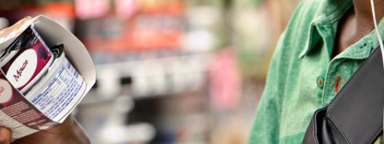 person holding yogurt in market - NSF Food & Label Compliance